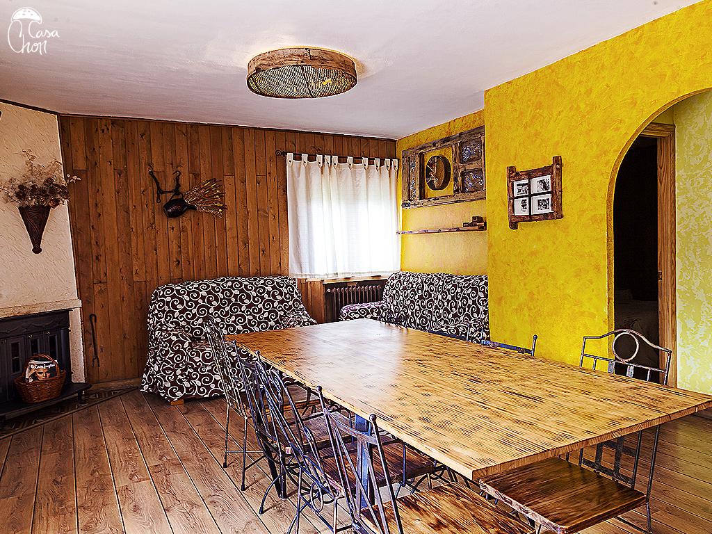 Salón con gran mesa y sofás para 5 personas, tiene chimenea